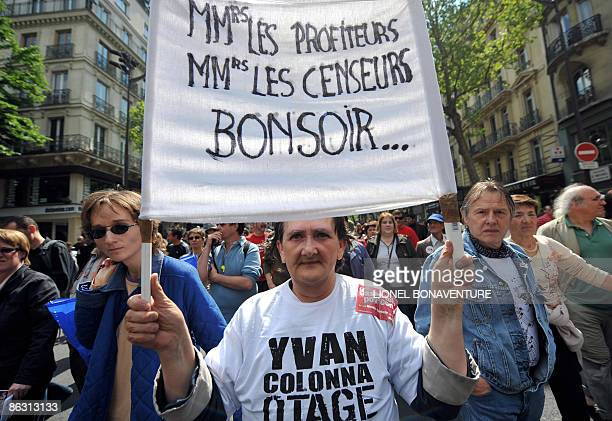 People hold a banner during the traditional May Day demonstration on May 1 2009 in Paris as leftwing opposition leaders and all of the country's...