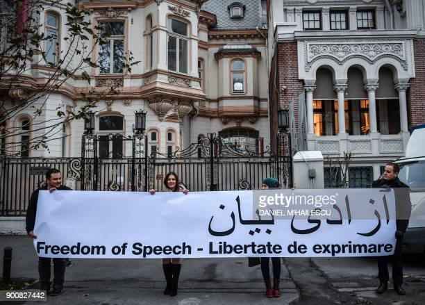 People hold a banner in support of protesters in Iran reading 'Freedom of speech' in English Romanian and Farsi on January 3 2018 during a protest...