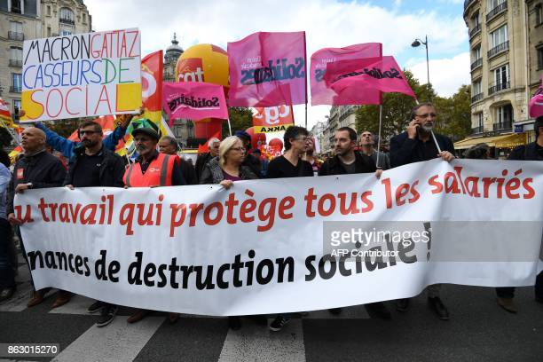 People hold a banner reading 'a work which protects all the employees' during a demonstration called by the CGT workers' union against the French...