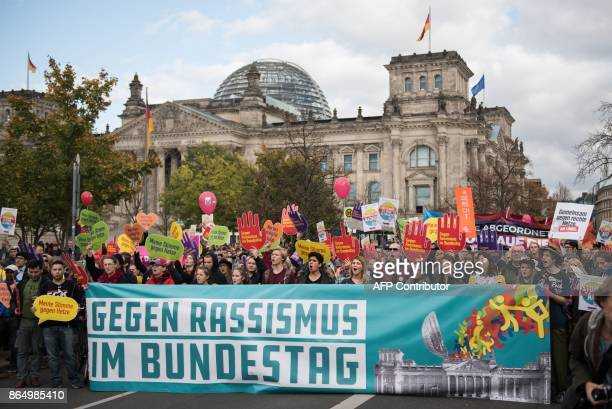 """People hold a banner reading """"against racism in the Bundestag lower house of parliament"""" as they pass by the Reichstag building to protest against..."""