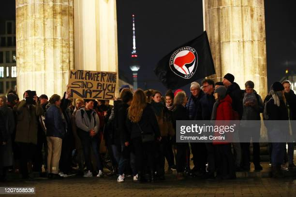 People hold a banner reading 'Followers are also nazis' and a antifascist movement flag as they gather for a vigil at the Brandenburg Gate to...