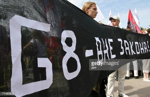 """People hold a banner reading """"G8 - out of the law"""" during a protest called by anti-globalisation activists and Communist supporters in central..."""