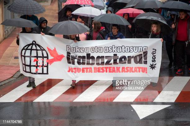 People hold a banner reading in Basque We will win peace and freedom Josu and the others free during a demonstration in the village of Miraballes on...