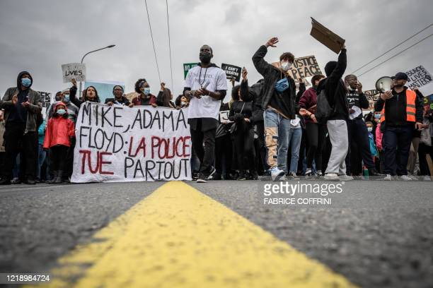 People hold a banner reading Mike Adama Floyd police kill all over as they take part in a rally on June 9 2020 in Geneva during a demonstration...