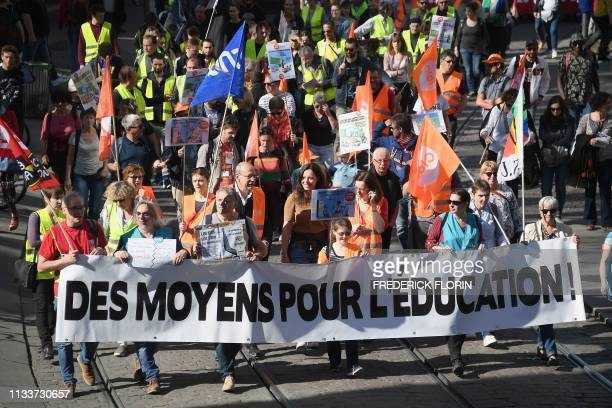 """People hold a banner reading """"More funds for education"""" as they take part in a demonstration called by several French national Education unions on..."""