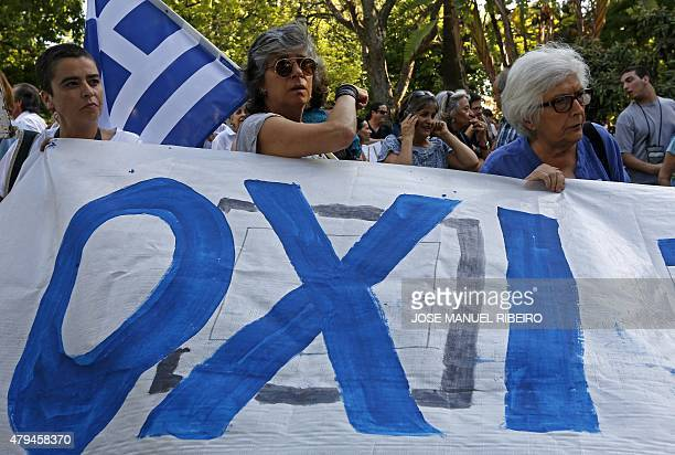 People hold a banner reading 'OXI' moments before a demonstration in support of Greece in Lisbon on July 4 2015 a day before nearly 10 million Greek...
