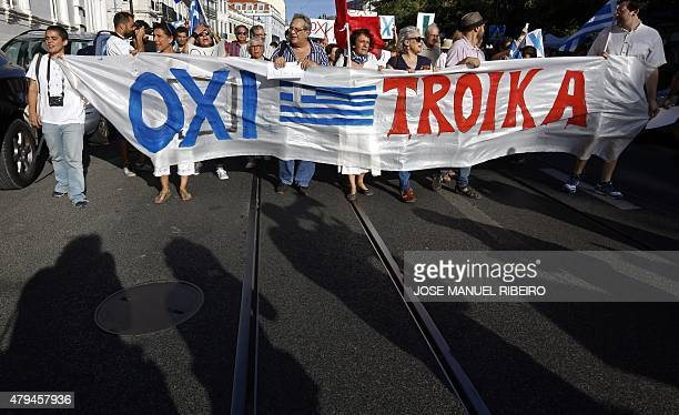 People hold a banner reading 'Oxi Troika' as they take part in a demonstration in support of Greece in Lisbon on July 4 2015 a day before nearly 10...