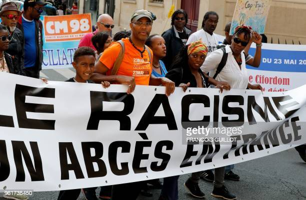 People hold a banner reading 'Racism is an abscess in France' as they take part in a march in memory of victims of slavery on May 23 in Paris The...