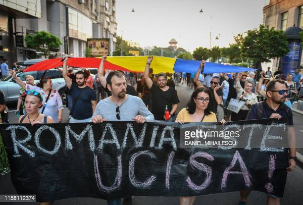 People hold a banner reading Romania is killed as they march in Bucharest July 27 2019 to commemorate Alexandra the 15yearold girl who has been...
