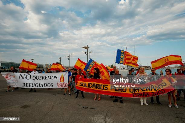 People hold a banner reading 'We don't want refugees' during a demonstration called by the farright political party Espana 2000 against the arrival...
