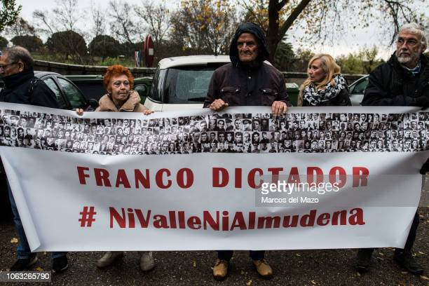 People hold a banner that reads 'Franco dictator' protesting at the Valley of the Fallen against the possible exhumation and transfer to the...