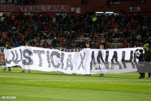 People hold a banner to demand justice for the femicide of 16yearold Anahí Benitez in Buenos Aires prior a second leg match between River Plate and...