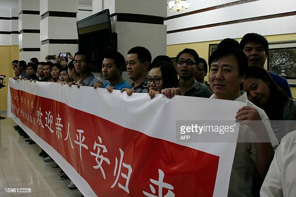 People hold a banner to welcome Chinese workers abducted by Darfur rebels earlier this month who arrive at the Khartoum airport after their release...