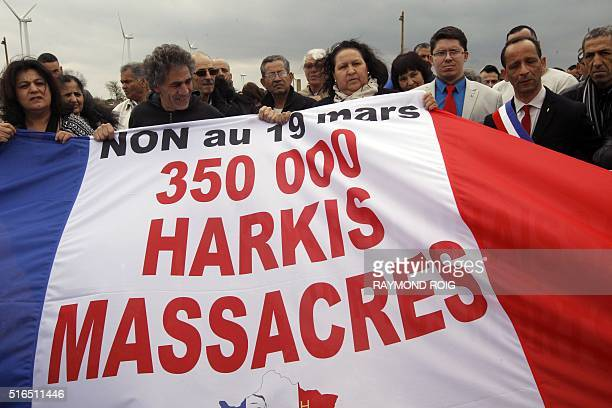 People hold a banner which translates as 'No to the March 19 350000 harkis massacred ' during a demonstration on March 19 2016 in Rivesaltes to...