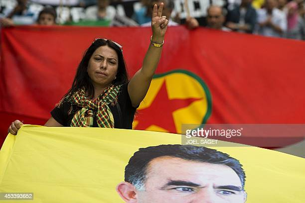 People hold a banner with the portrait of Kurdish rebel leader Abdullah Ocalan during a demonstration in Paris on August 9 2014 in support of the...