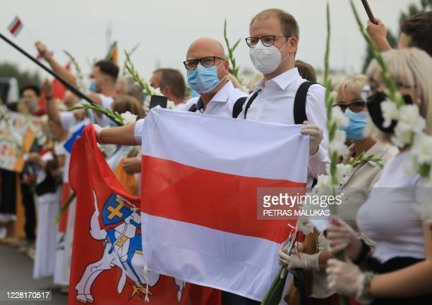 People hold a Belarussian opposition flag as people form a human chain from Vilnius to Medininkai along the border with Belarus to show solidarity...