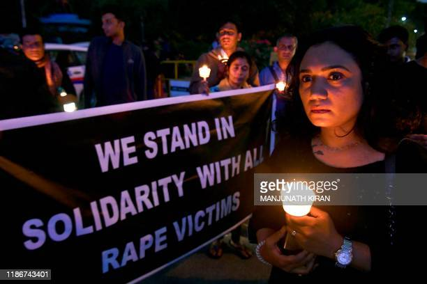 People hold a candlelight vigil in support of sexual assault victims and against the alleged rape and murder of a 27-year-old veterinary doctor in...