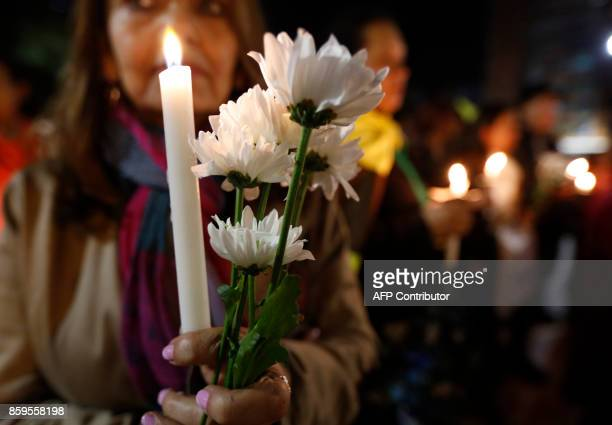People hold a candlelight vigil to honor farmers killed during an October 5 protest by coca growers in a rural area of Tumaco in the southwest...