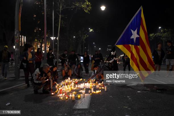 People hold a Catalan flag and light candles during a protest against the jailing of Catalan separatists in Mallorca Street near the Spanish...