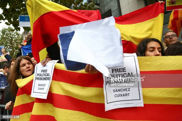 People hold a Catalan flag during a demonstration of pro and anti Catalan independance in front of the Press Club in Brussels on October 31 2017...