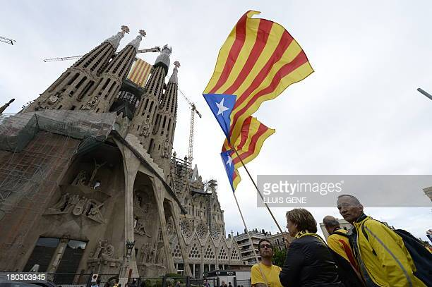 People hold a Catalonian flags infront of the basilica Sagrada Familia during a campaign seeking independence from Spain and marking Catalonia...