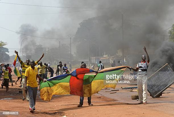 People hold a Centrafrican flag as they protest against the French Sangaris intervention in the Galabadia neighborhood close to the Centrafrican...