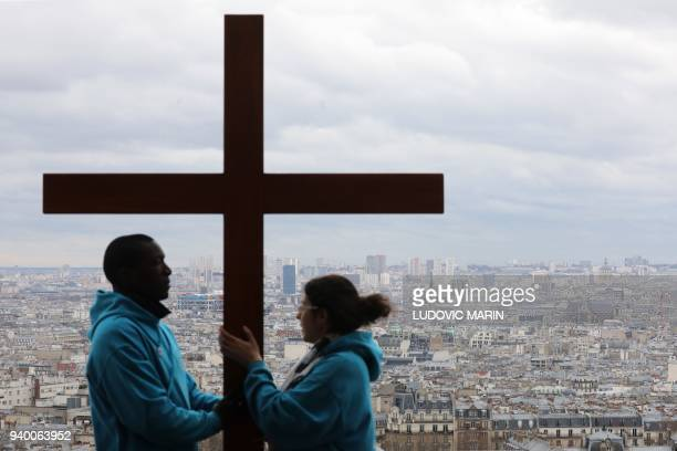 People hold a cross during a Stations of the Cross procession on Good Friday in front of Sacre Coeur Basilica on Montmartre hill in Paris on March 30...