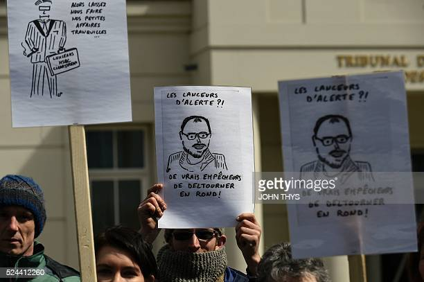 People hold a drawing depicting Antoine Deltour demonstrate outside the courthouse in Luxembourg on April 26 in support of whistleblower Antoine...