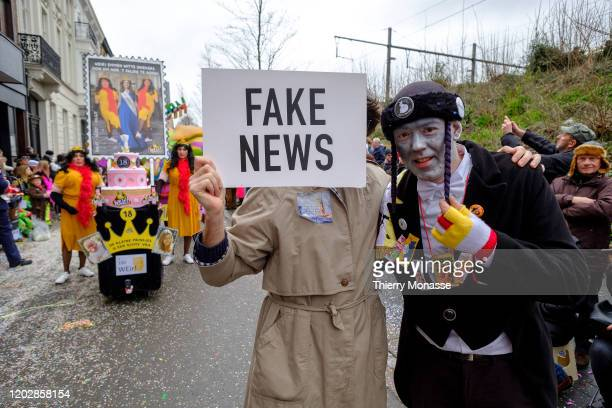 People hold a Fake News sign during the 92nd edition of the Aalst Carnival parade on February 23 2020 in the streets of Aalst Belgium The Aalst...