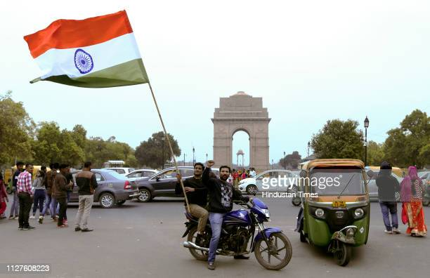 People hold a flag as they celebrate reports of IAF air strikes across LoC on February 26 2019 in New Delhi India Indian forces carried out a strike...