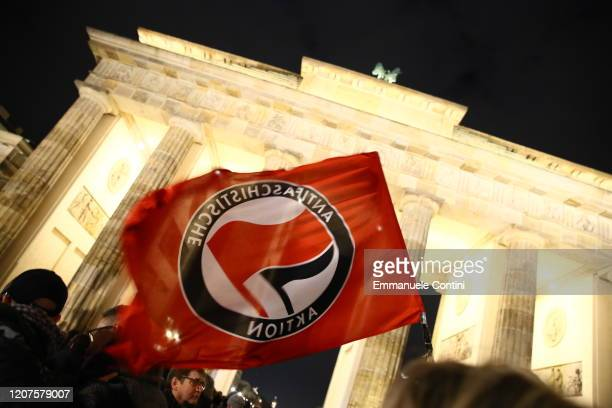 People hold a flag of the anti fascist movement during a vigil at the Brandenburg Gate to commemorate the victims of the Hanau shootings on February...