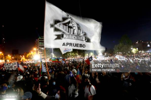 """People hold a flag that reads """"Approval"""" during a celebration as waiting for the official results of the referendum for a new constitution on October..."""