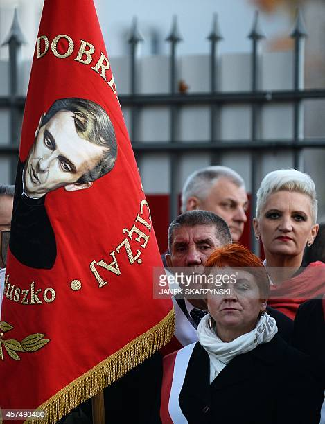People hold a flag with picture of Jerzy Popieluszko during ceremonies in front of his parish church in Warsaw on October 19 2014 Poland marks 30...