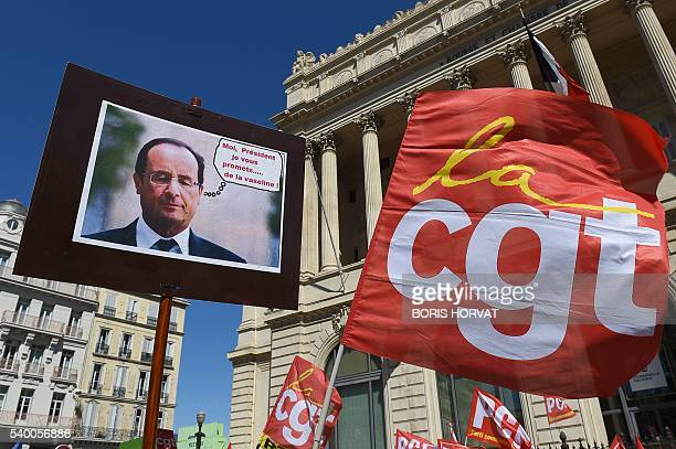 People hold a French president picture and a flag of French union Confederation generale du travail during a demonstration against the French...