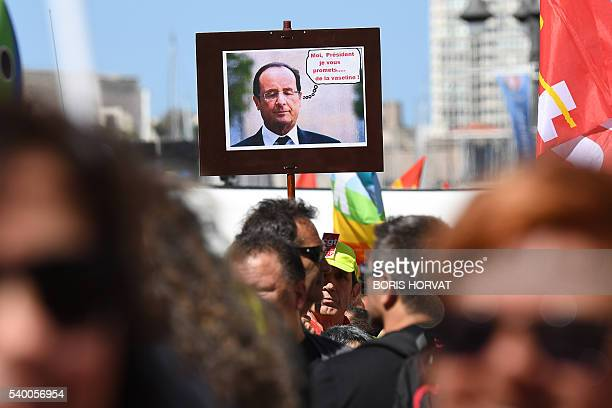 People hold a French president picture with a sign reading As a president I promise you vaseline during a demonstration against the French...