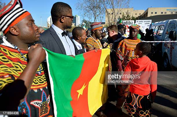 People hold a Ghanaian flag as they stand oustide the Mediclinic Hear hospital on June 28 2013 in Pretoria A gravely ill Nelson Mandela showed...