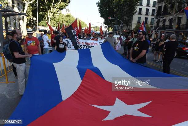 People hold a giant national Cuban flag during the celebration of the Cuban Revolution's anniversary in Madrid