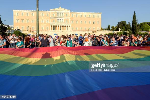 People hold a giant rainbow flag in front of the Greek parliament during the city's 6th Gay Pride march in Athens on June 10 2017 / AFP PHOTO /...
