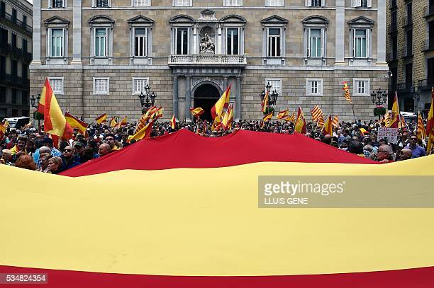 People hold a giant Spanish flag in front of Catalonia's government headquarters during a demonstration in support of the Spanish army organized by...
