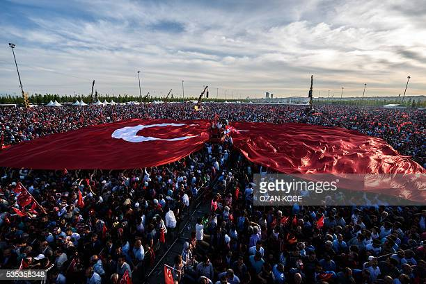 TOPSHOT People hold a giant Turkish national flag as Turkish President speaks during a rally to mark the 563rd anniversary of the conquest of...