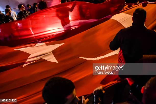 TOPSHOT People hold a giant Turkish national flag during a demonstration on December 11 2016 a day after twin bombings near the home stadium of...