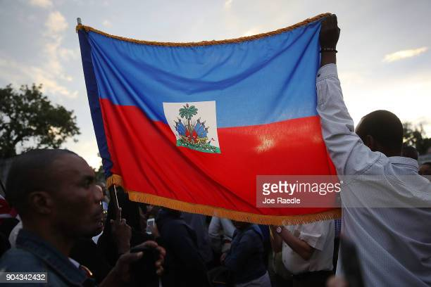 People hold a Haitian flag as they gather together to mark the 8th anniversary of the massive earthquake in Haiti and to condemn President Donald...