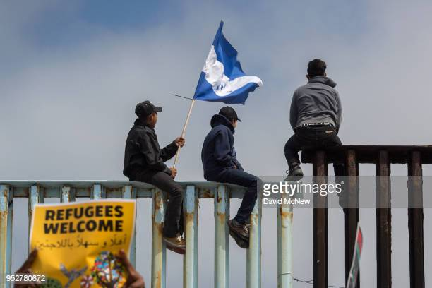 People hold a Honduran flag and look into the United States from atop a section of border fence as members of a caravan of Central American asylum...