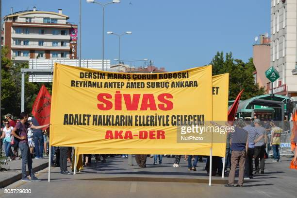 People hold a huge banner during a march to the 24th anniversary of the Sivas massacre in Ankara on July 02, 2017. In 1993, 35 people were killed...