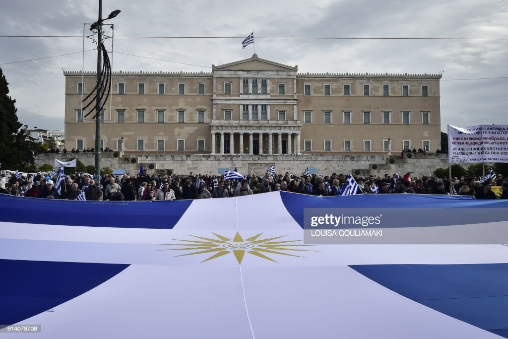 People Hold A Huge Flag Of Greece Bearing The Vergina Sun C