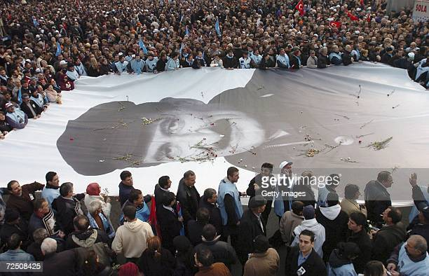People hold a huge portait of former Prime Minister Bulent Ecevit as they march during his funeral on November 11 2006 in Ankara Turkey The fivetime...