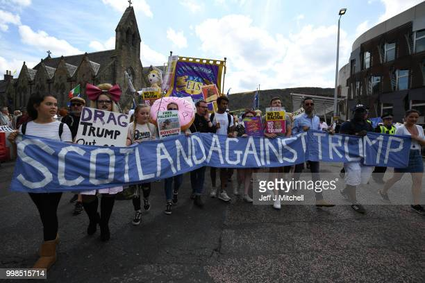 People hold a large antiTrump banner and other signs while the US President is visiting Trump Turnberry Luxury Collection Resort in Scotland as...