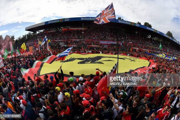 People hold a large banner with the logo of Scuderia Ferrari after the Italian Formula One Grand Prix at the Autodromo Nazionale circuit in Monza on...