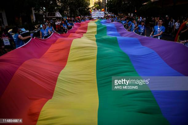 TOPSHOT People hold a large rainbow flag as they take part in the Athens Gay Pride in Athens on June 8 2019 Thousands marched in the 15th annual...