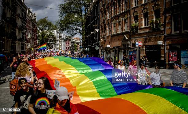 People hold a large rainbow flag during the Pride Walk through the center of Amsterdam on July 29 2017 The march marks the beginning of Pride...